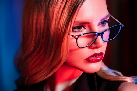 A close up portrait of a confident lady wearing glasses. Beauty, make-up, style. Stock Photo