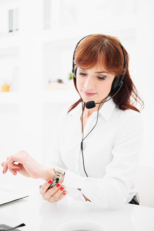A portrait of a beautiful woman sitting at the desk with a headset at the workplace. Beauty, fashion. Work, education.