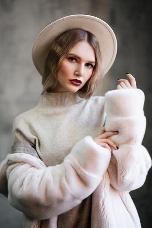 A portrait of thoughtful beautiful girl wearing a white fur coat. Beauty, winter fashion.