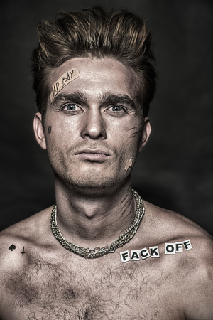 Bad boy concept. Close-up portrait of a bad guy showing rudeness and aggression on black background. Rocker, punk. Stock Photo