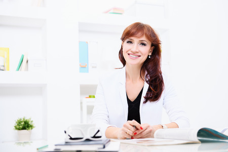 A portrait of a beautiful woman sitting at the desk at the workplace. Beauty, fashion. Work, education.