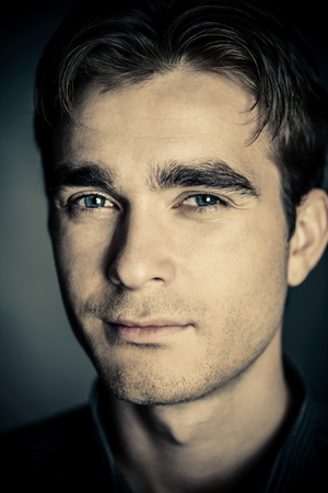Close-up portrait of a handsome young man on black background. Male beauty. Mens health.