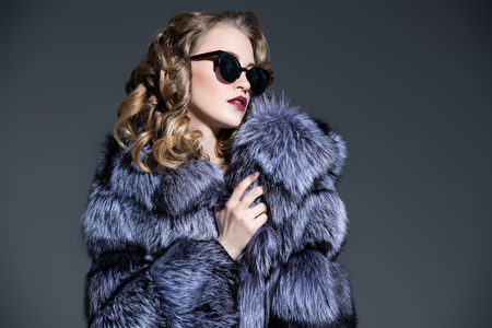 A close up portrait of a beautiful woman wearing a fur coat with hood and sunglasses. Beauty, winter fashion, style.