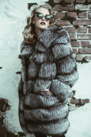 A portrait of a beautiful girl wearing a fur coat. Beauty, winter fashion. Stock Photo