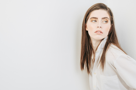 A portrait of a beautiful dark-haired young woman wearing a white shirt posing over the white background. Beauty, cosmetics, fashion.