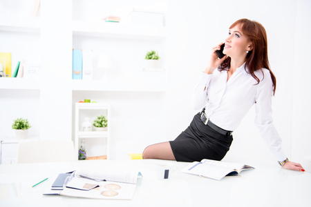A portrait of a beautiful woman sitting at the desk and talking on the mobile at the workplace. Beauty, fashion. Work, education. Stock Photo