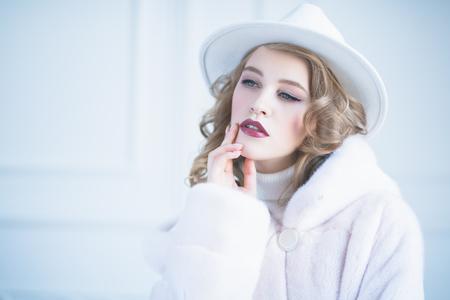 A portrait of thoughtful beautiful woman wearing a white fur coat. Beauty, winter fashion.