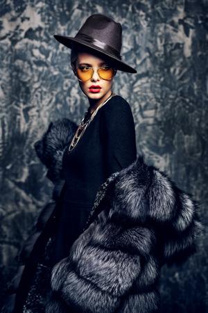 Portrait of a beautiful woman in luxurious fur coat posing in studio. Luxury, rich lifestyle. Fashion shot.