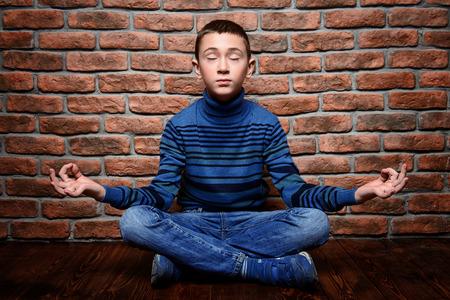 Meditating boy on brick wall background. Kids fashion. Winter clothes.