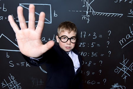 Smart schoolboy in black suit and glasses explaning something emotionally at the blackboard. Educational concept. Stock Photo