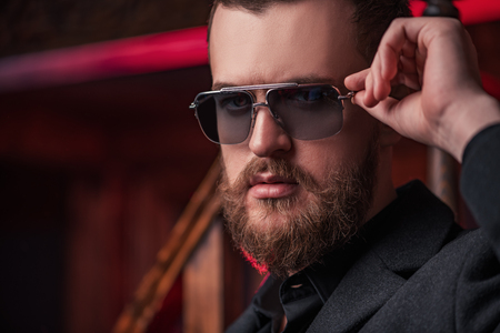 A portrait of a stylish man wearing sunglasses. Beauty and style for men. Stock Photo