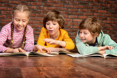 Happy smiling children reading books together. Educational concept. Stock Photo