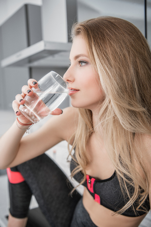 Portrait of a beautiful sexy girl in jogging suit sitting with a glass of water at the kitchen in home. Fitness at home. Beauty, fashion.