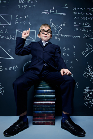 Smart schoolboy in black suit and glasses is sitting on books on  background of blackboard. Educational concept. Stock Photo