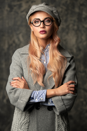 A portrait of a fashionable bright lady posing in studio over grunge background. Fashion for women.