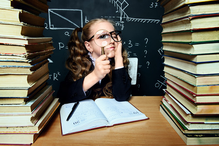Portrait of a smart schoolgirl in glasses posing with books and magnifier over school blackboard. Educational concept.
