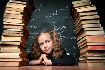 Portrait of a smart schoolgirl in glasses posing with books over school blackboard. Educational concept. Stock Photo