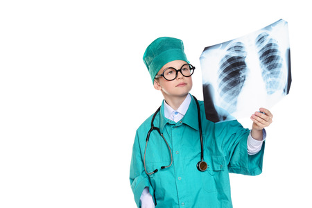 Cute smiling boy dressed like a doctor holding radiograph. Different occupations. Pediatrics. Isolated over white.