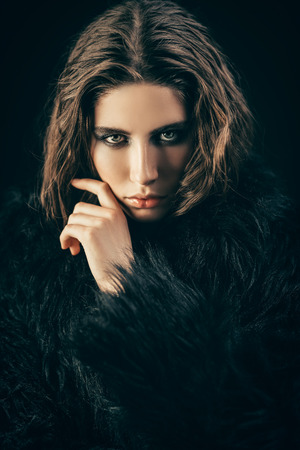A portrait of a beautiful gorgeous girl in black posing in the studio over the black background. Beauty, fashion. Stock Photo