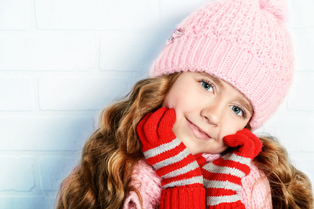 Winter clothes concept. Pretty smiling girl with long curly hair wearing pink knitted hat and scarf and smiling at camera. Stock Photo