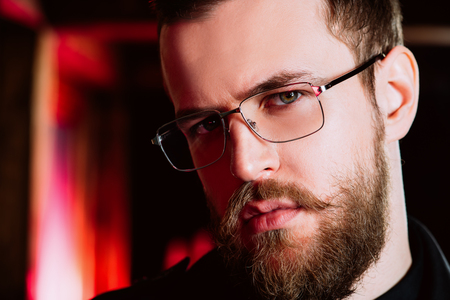 A close up portrait of a stylish man wearing glasses. Beauty and style for men.
