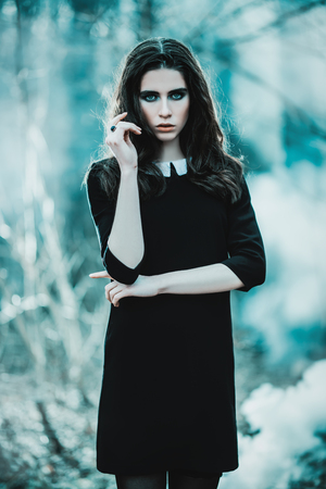 A portrait of a beautiful mysterious girl in black posing in the forest. Beauty, fashion, nature.