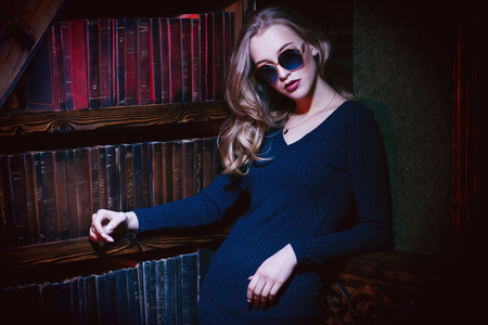 A portrait of an elegant lady wearing jumper and sunglasses. Beauty, make-up, style.