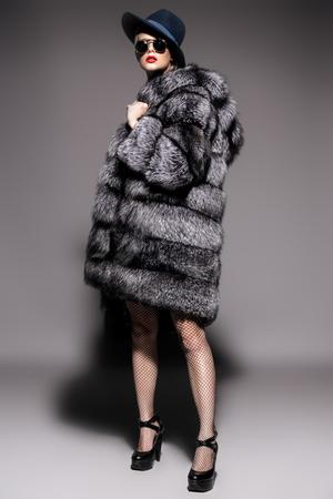 Beautiful woman in luxurious fur coat posing in studio. Luxury, rich lifestyle. Fashion shot. Stock Photo
