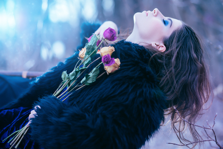 A portrait of a beautiful mysterious girl in black posing on the armchair in the forest with flowers. Beauty, fashion, nature.