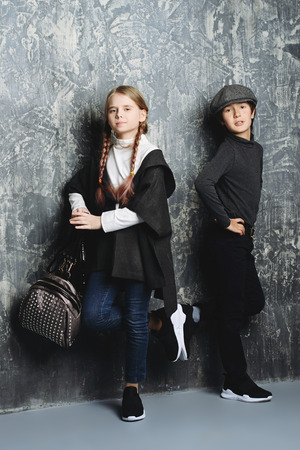 Kid's fashion. Two modern children posing together at studio. Clothes for children. 版權商用圖片