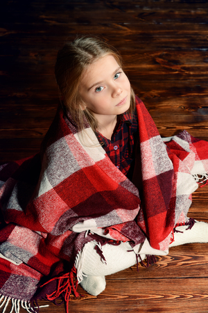 Ð¡ute girl is sitting covered with a plaid on a floor. Children's fashion. Stok Fotoğraf