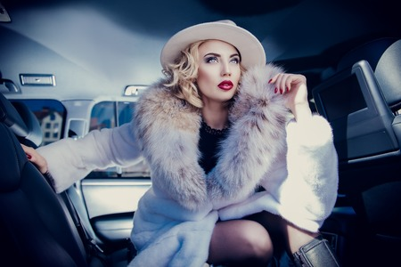 A portrait of a gorgeous blonde lady posing in a car. Car, fashion, beauty, chick.