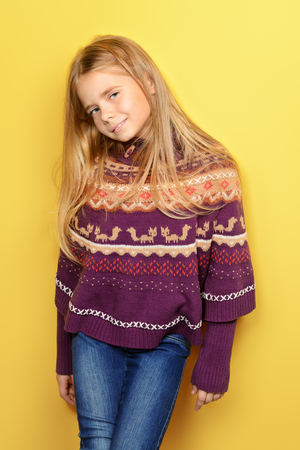 Kids fashion. Portrait of a cute 7 year old girl wearing knitted clothes posing over bright yellow background. Autumn, winter fashion. Happy child girl.