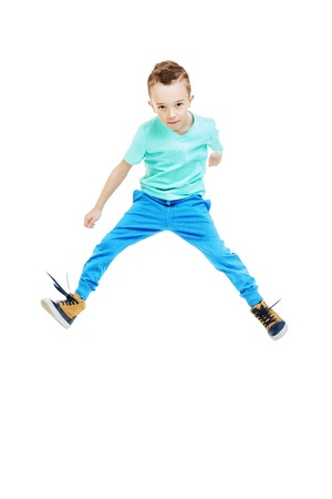 A full length portrait of a handsome child boy jumping in the studio over the white background. Kids, fashion, casual style. Фото со стока