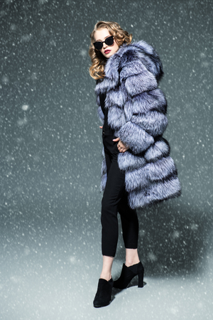 A full length portrait of a beautiful woman wearing a fur coat with hood and sunglasses. Beauty, winter fashion, style.