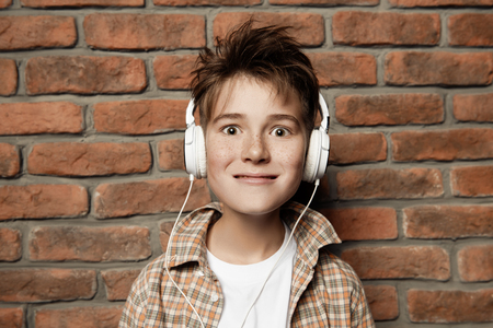 A portrait of a young boy with headphones in casual clothes posing over the brick wall. Fashion for male teenagers.
