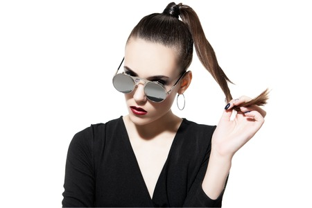 A close up portrait of a fashionable young lady posing in the studio over the white background. Style, beauty, fashion.
