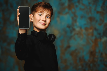 A portrait of a young boy with a smartphone and headphones on grunge background. Fashion, gadgets.