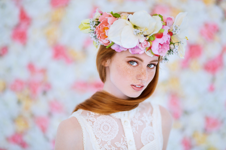 A portrait of a lovely beautiful girl with a wreath of flowers on the head on a floral background. Beauty, cosmetics. Stock Photo - 124093105
