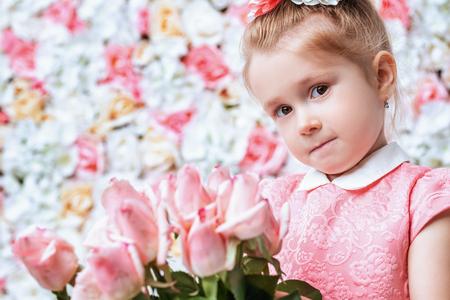 Un portrait en gros plan d'une jolie fille enfant qui pose en studio sur le fond avec des fleurs. Enfants, été, beauté.