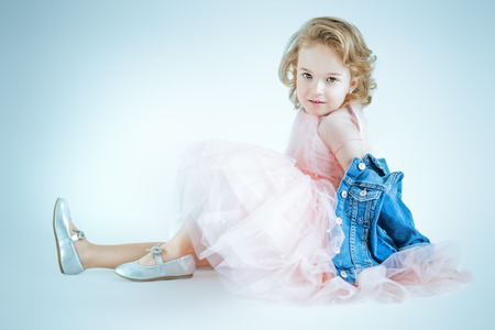 A full length portrait of a pretty girl in a pink dress and a denim jacket posing in the studio over the white background. Kids, fashion, beauty. Stock fotó