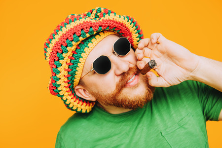 A portrait of a bright man posing in the studio over the yellow background and smoking a cigar. Men, beauty, colors, fashion, style.