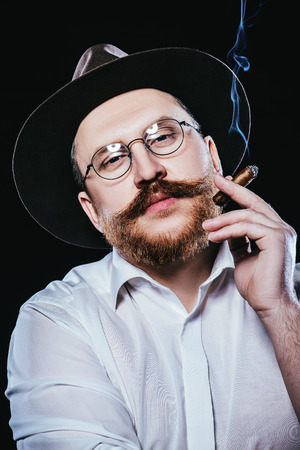 A close up portrait of a thoughtful man with a cigar posing in the studio over the black background. Men's beauty, fashion, style.