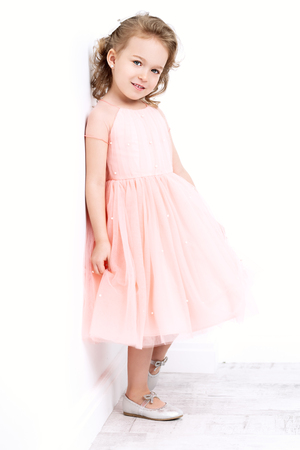 A full length portrait of a pretty girl in a pink dress posing in the studio over the white background. Kids, fashion, beauty.