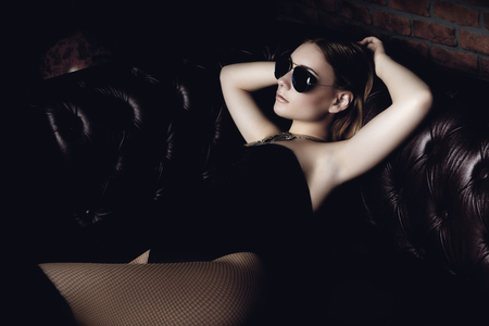 Attractive young woman lies on a leather sofa in a tight black lingerie. Beauty, underwear fashion.