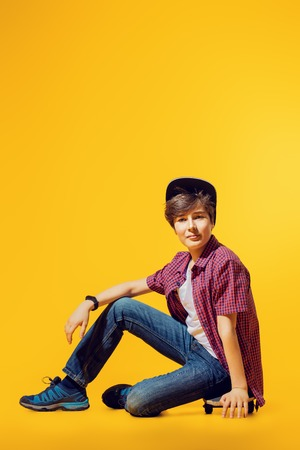 A full length portrait of a bright young boy posing in the studio over the yellow background with a skateboard. Kids, fashion.