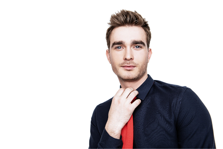 A close up portrait of a fashionable young man posing in the studio over the white background. Casual fashion for men.