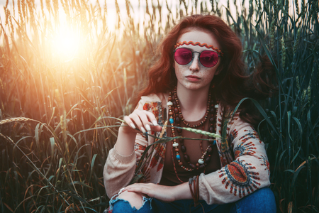 A portrait of a fashion female model sitting on the grass. Contemporary bohemian style. Spirit of freedom. Fashion shot. Bohemian, bo-ho style. Stock Photo