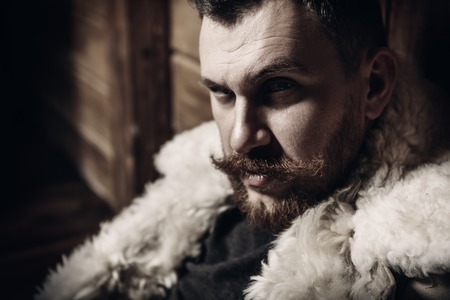 A close up portrait of a brutal mature man posing at the wooden house. Man, beauty.