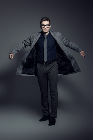 A portrait of a fashionable young man posing in movemant in the studio over the grey background. Formal fashion for men.